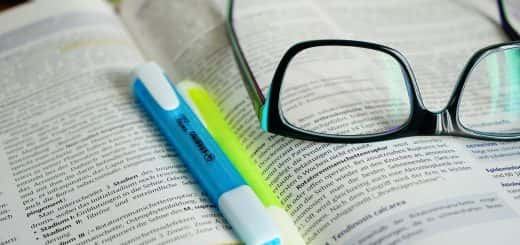 Pair of spectacles and highlighter pens sitting on an open textbook