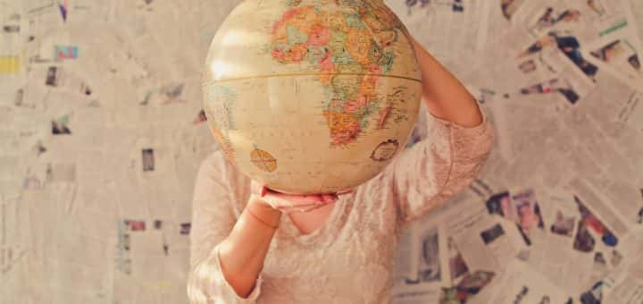 Photo: person holding a globe over their face