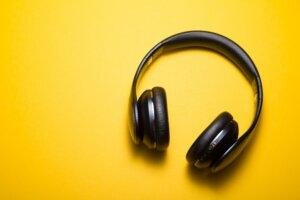 black headphones on yellow background, music, listening, podcast