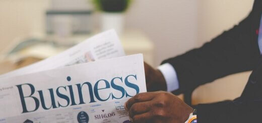 man's hands holding newspaper that has the title 'Business'